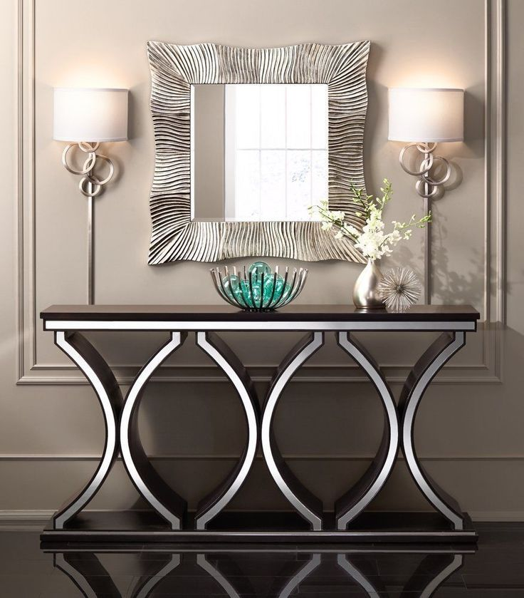 A rich chocolate brown finish enhances the distinctive design of this spacious contemporary console table that features glistening mirror detail on the top and bottom lip as well as on its wonderful base.