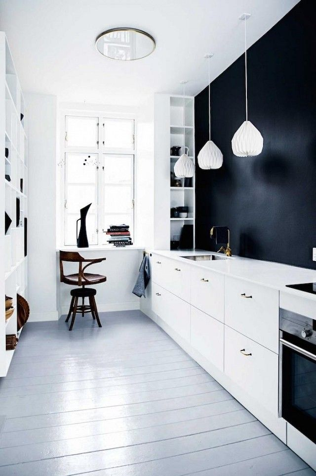 Minimalist galley kitchen with a black statement wall, white lanterns, and white cabinets