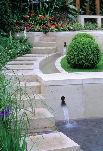 Contemporary style water feature with steps, rill and retaining wall, border beds, buxus sphere balls, bench seats. RHS Chelsea 2004.