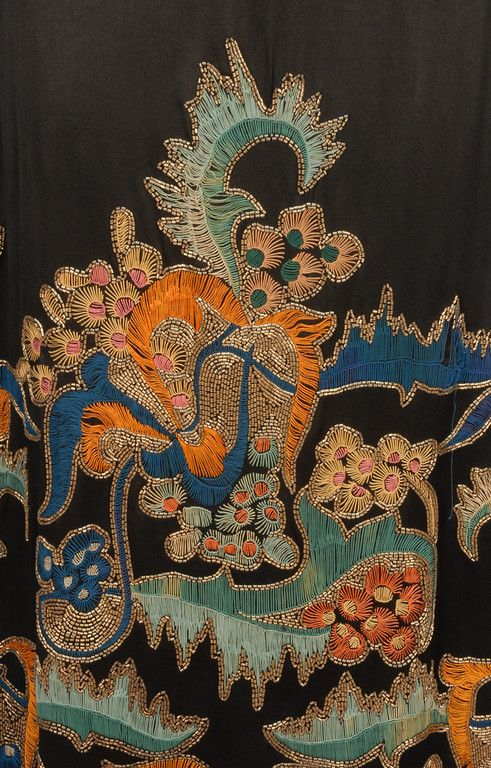 DOEUILLET EMBROIDERED and BEADED EVENING DRESS, 1920's. Sleeveless black silk charmeuse heavily embroidered in vibrant shades of orange, aqua, blue, pink and yellow with gold bugle beads in an abstract floral on the upper back and over-skirt front and sides, self sash having back loop and drape, cream silk under dress having applied lace to the sides.