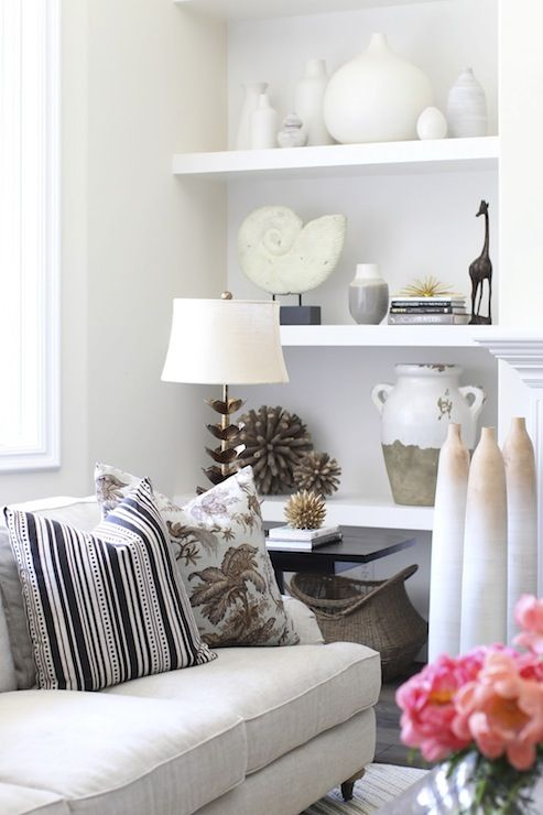 Gorgeous living room with floatings shelves accented with collection of white pottery, snail statue, gray vase, giraffe statue filling alcoves on either side of fireplace.