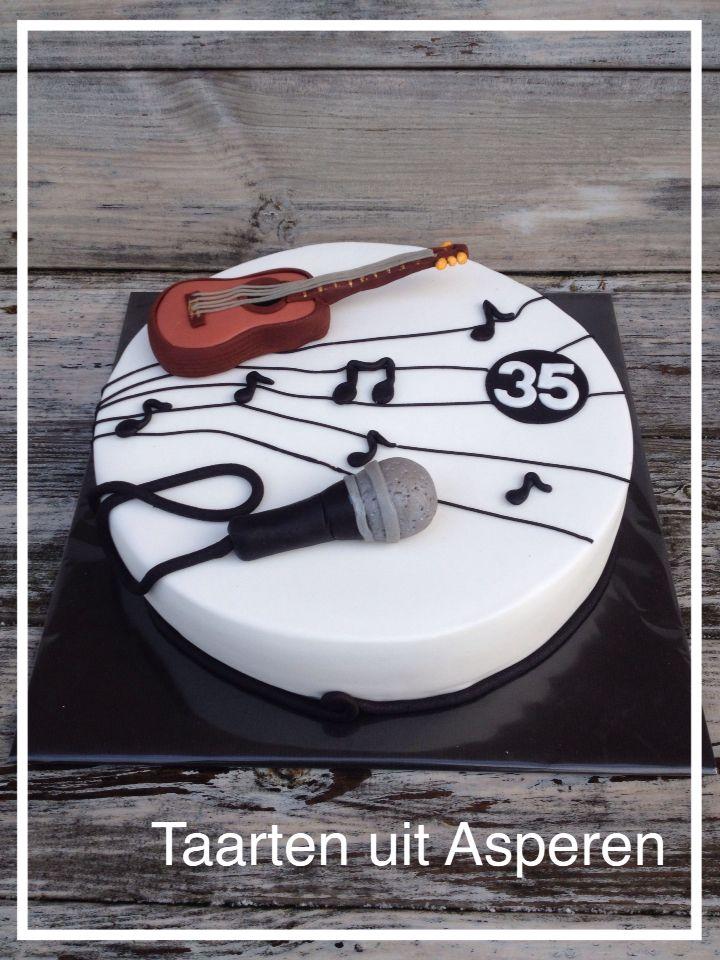 Een taart met muzieknoten, microfoon en een gitaar