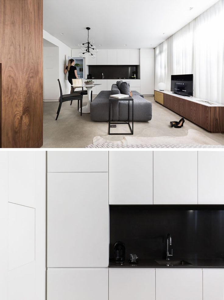 Along One Wall Of This Small Apartment Is The Kitchen With Bright White  Cabinets And Black