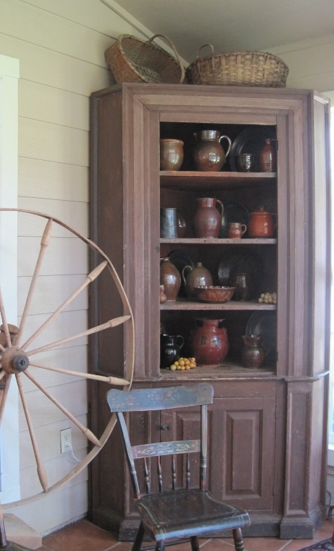 Old Corner Cupboard Filled With Stoneware Crocks, Jugs And Old Spinning  Wheel.