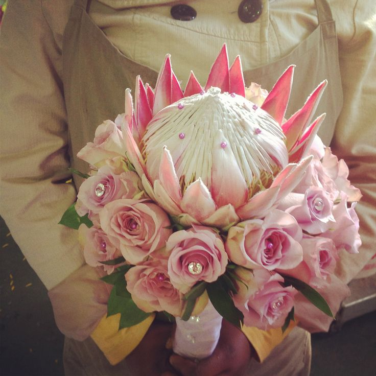 King protea surrounded by roses in shades if pink