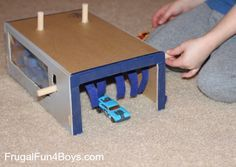 Use a cardboard box, dowel rods, and felt to create a car wash toy for Hot Wheels cars.