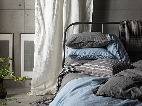 Close-up of a black metal bed with bedlinen in light blue and gray.