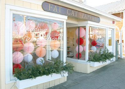 This is similar to how I envisioned my store front to look, if and when I can ever justify opening a store!   I love the tissue paper balls hanging in the window!  So cheerful and happy!