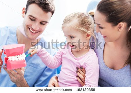 Dentist teaching girl how to brush teeth  - stock photo