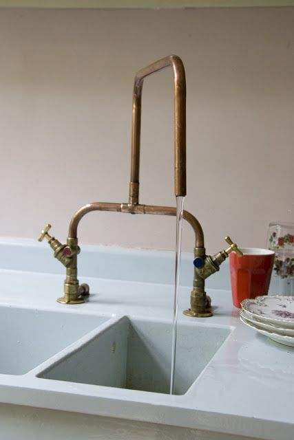 Beautiful exposed copper pipe kitchen faucet over deep sink.