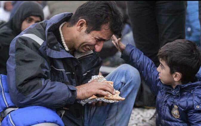 A syrian man is crying while trying to feed his son . Help syrian refugees