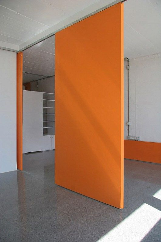 Orange wall concrete floor room divider ideas for Sliding door partition wall