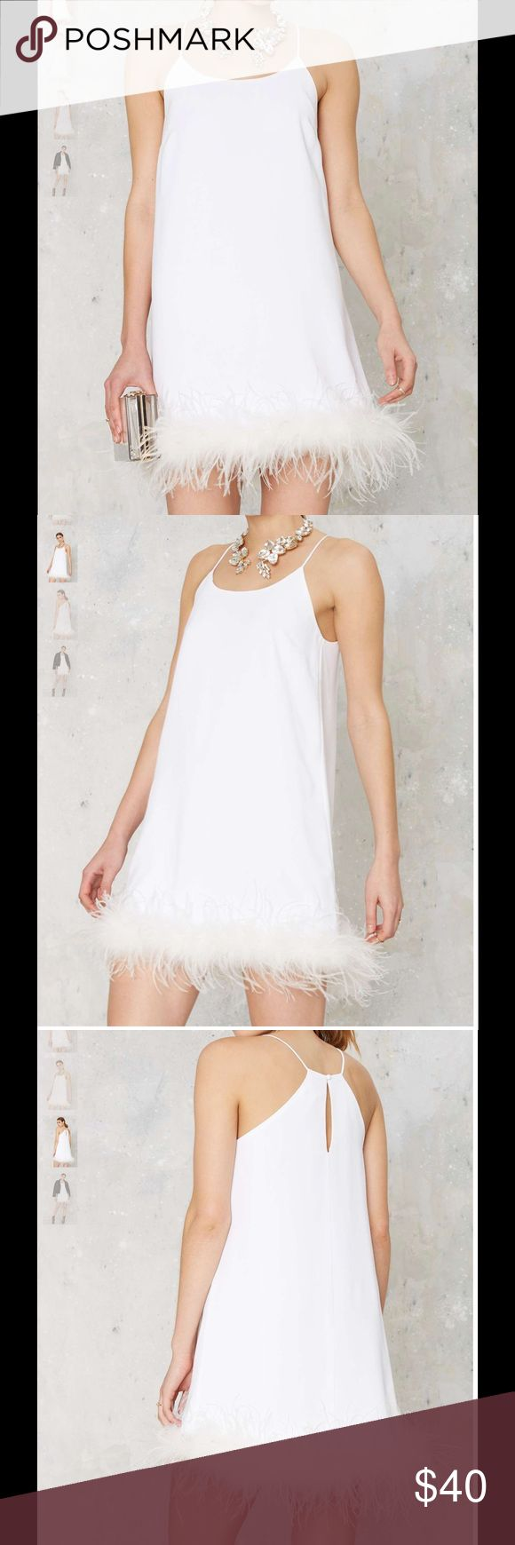 #69D time after time feather dress 🐥💚 A feather trim is kinda timeless (meaning we'll never get over it). This dress is white and features feather trim at hem, scoop neck, and keyhole cutout with button closure at back. Fully lined. Perfect for, well, every party ever.  *Polyester/Ostrich Feather/Spandex  *Runs true to size  *Model is wearing size XS  *Hand wash cold  *Imported Nasty Gal Dresses Mini
