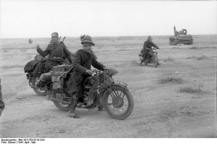 North Africa, 1941: Italian military motorcyclists meet with a German patrol in the desert. These moto men were brave souls. Crossing large swaths of desert on those earlier machines took bravery, mechanical skill, and the ability to see (or, try at least) in sand storms. Those who survived had truly earned their wings.
