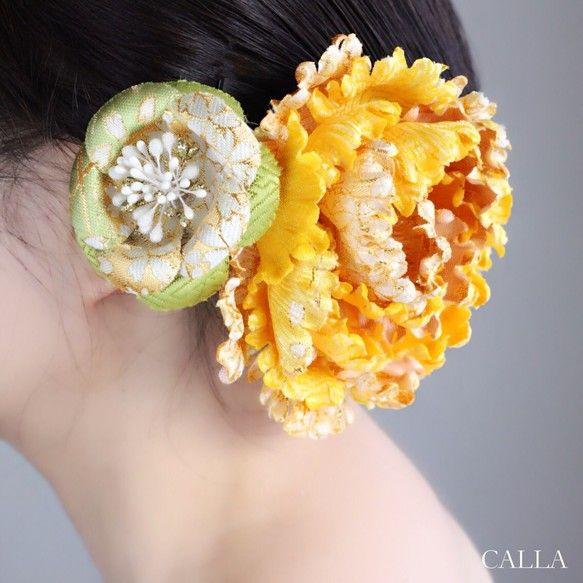 結婚式、成人式、パーティーetcに合わせて様々な組み合わせでアレンジできる2パーツからなるヘアアクセサリーです。和柄の生地で作られた豪華な雅牡丹と若草色の椿の組み合わせです。日本人の黒髪に綺麗に映えるお色目で見ているだけで心が華やぎます♪安心して保管して頂けるスクエアボックス(black 直径13㎝)にお入れしてお届け致します。素材 アーティフィシャルフラワーsize  雅牡丹   直径12㎝   Uピン型        椿         直径6.5㎝  かんざし型ギフトラッピングはボックスにリボンをおかけしてご用意致します。       #Creemaポイント10倍