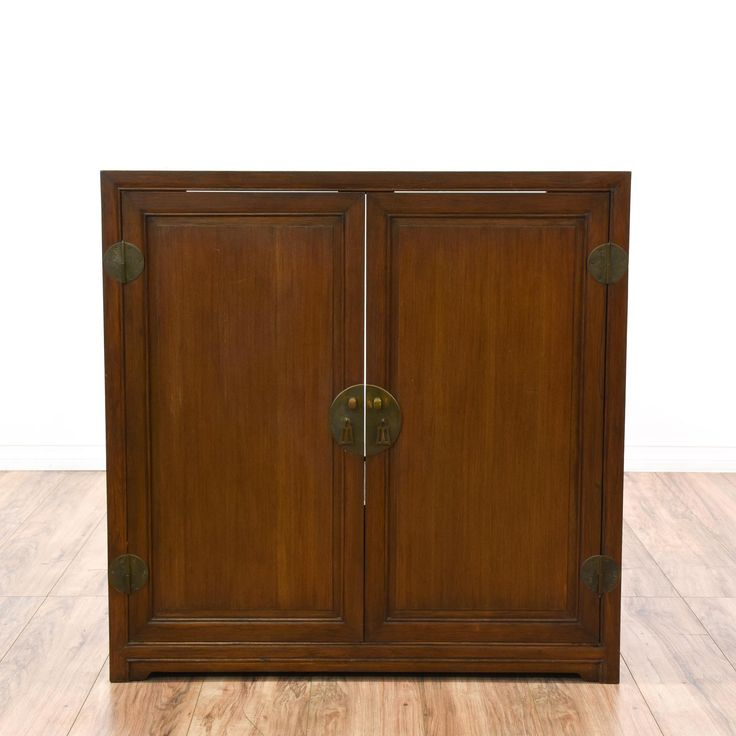 This asian style cabinet is featured in a solid wood with a gorgeous walnut finish. This bar buffet has 2 carved panel doors, distressed brass hardware and a large cabinet interior with woven accents. Converted stereo cabinet perfect for storing drinks! #asian #storage #cabinet #sandiegovintage #vintagefurniture