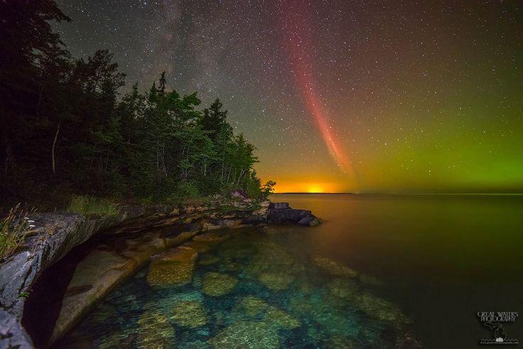 la luminosidad amarilla del horizonte proviene de la ciudad de Marquette (Michigan ,  EE.UU.). En primer plano, las rocas azules y amarillas del  Lago Superior están iluminadas por una linterna LED. A la izquierda del arco de protones rojo está la banda de la  Vía Láctea .