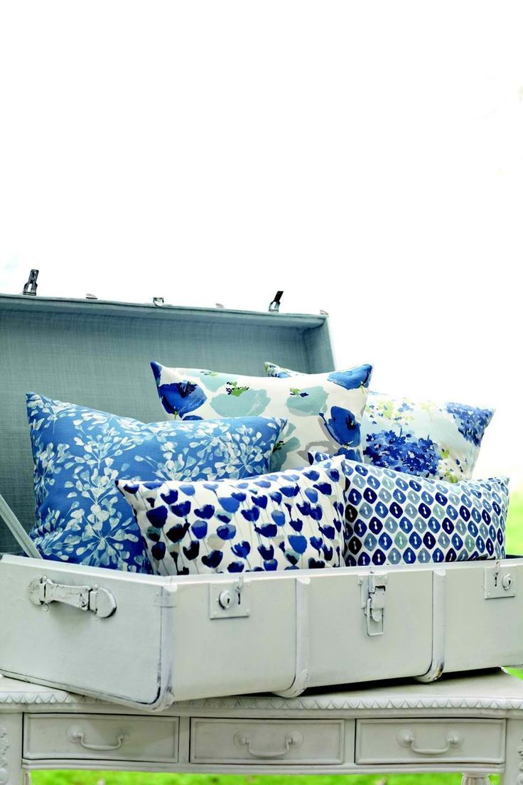 Beautiful display of handmade pillows in a painted trunk at a craft fair or market.