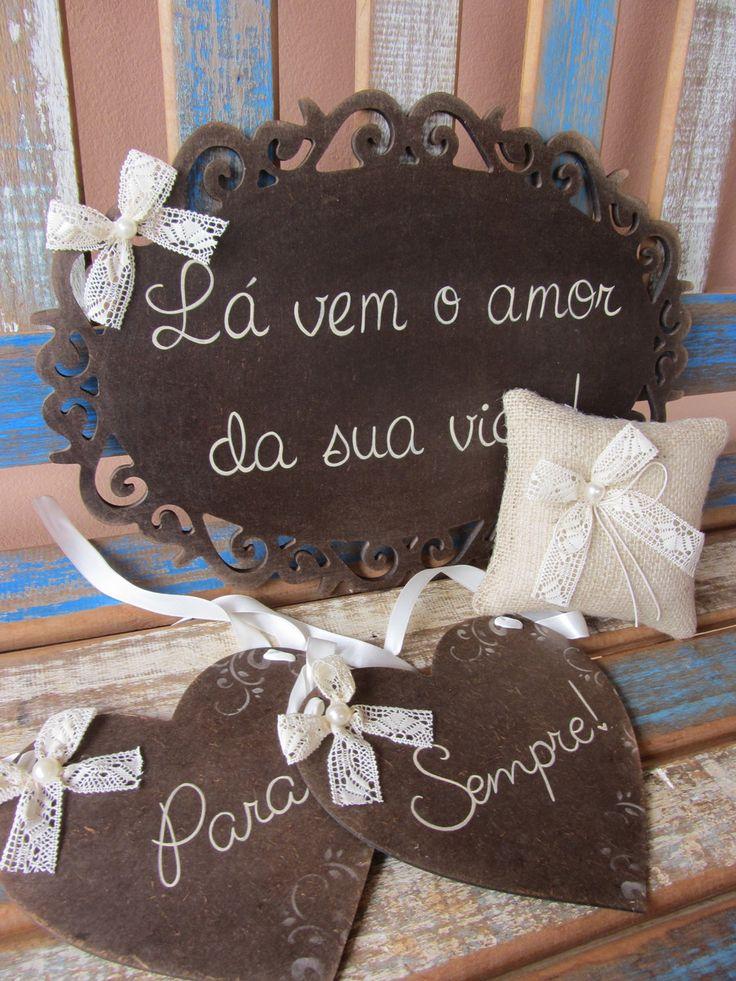 Kit promocional para Casamento <br> <br>Placa para cadeira dos noivos: Placas em madeira MDF, customizadas e manuscritas artesanalmente. Formato de coração, pintadas em betume marrom café, com fita de renda de algodão pérola e detalhe de pérola. <br>Opcional a escolha da fita de cetim. <br>Altura: 18.00 cm <br>Largura: 0.30 cm <br>Comprimento: 17.00 cm <br> <br>Almofada artesanal rústica para alianças: Confeccionada com juta, renda na cor pérola, cordão de algodão e detalhe em pérola…