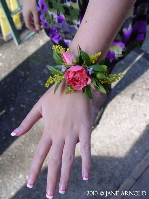 Wrist corsage  Pink spray rose, yellow solidaster and rosemary. Flowers and photo by The Wild Orchid floral design in Sebastopol.
