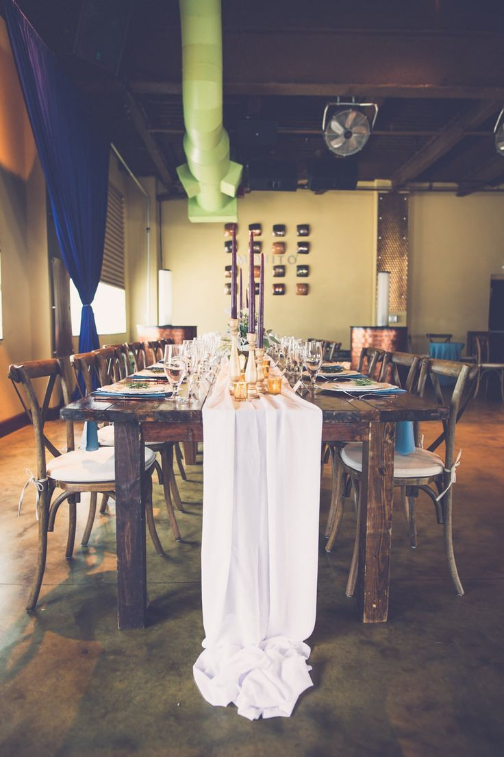 Boho Wedding Reception with Wooden Table, Wood X Back Chairs, Tall Burgundy Candles, Gold Accents, and Navy Blue Drapery   Tampa Bay Hotel Wedding Reception Venue Crowne Plaza Tampa   Tampa Farm Table Rentals A Chair Affair