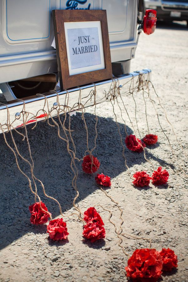 Flowers tied to the back of a car for a wedding
