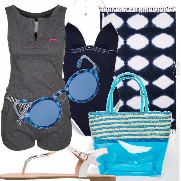 Costume intero blu con copricostume a tuta corta. Infradito in pelle bianchi con dettagli colorati. Borsetta mare trasparente color turchese e telo mare bianco blu per accompagnare questo look to go da spiaggia. Gli occhiali da sole blu scuro, tondi, ideali per un pomeriggio all'aria aperta.