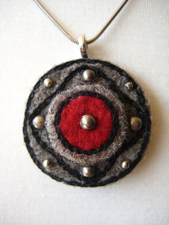 This is a round needle felted pendant, grey-red with black embroideries and decorated with metal beads. Metal loop. Measures: 5 cm long (with
