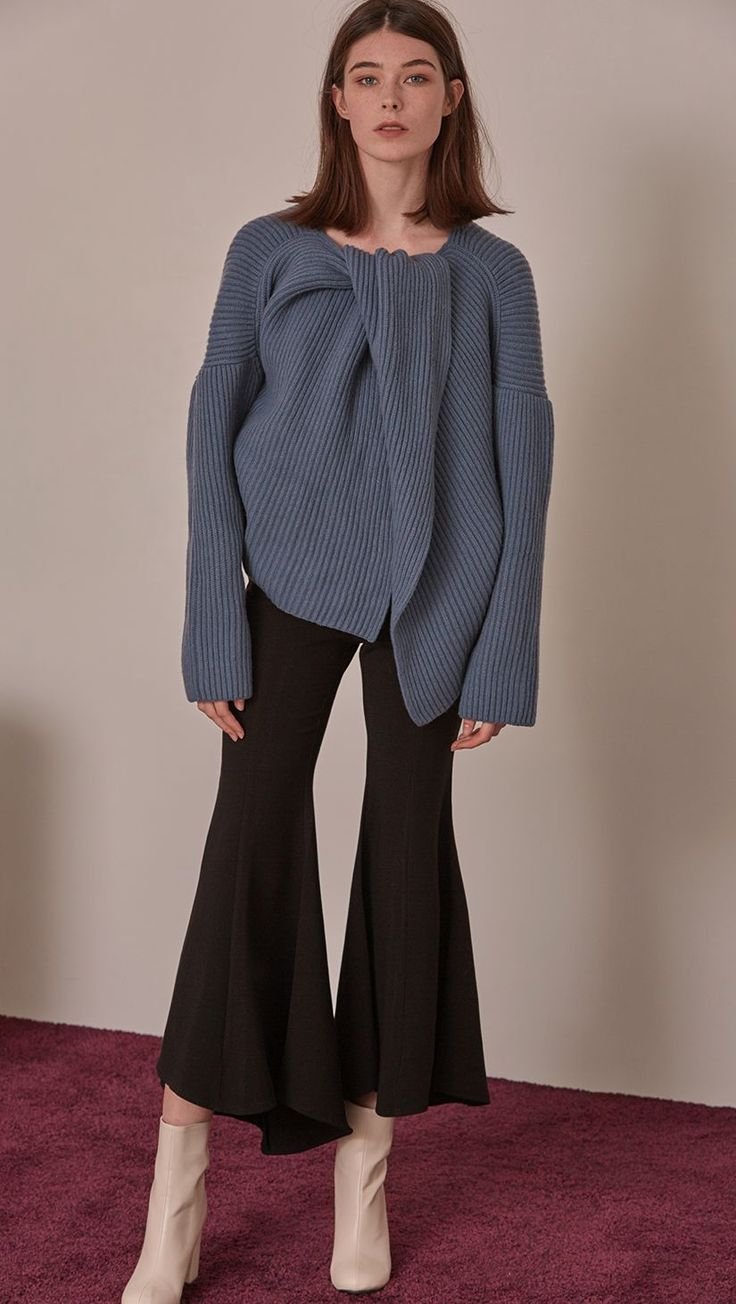 Darah Sweater in Blue. High-low length. Twisted opening collar with pointed wide round neckline. Drop shoulder design, open rib details. Short length in open back. Designed to be relaxed fit. Please n