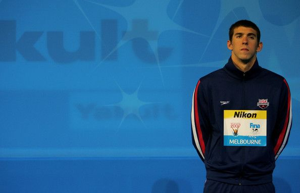 Michael Phelps Photos Photos - Michael Phelps of the United States of America waits to receive his gold medal after winning the Men's 100m Butterfly Final during the XII FINA World Championships at the Rod Laver Arena on March 31, 2007 in Melbourne, Australia. - XII FINA World Championships - Day 15
