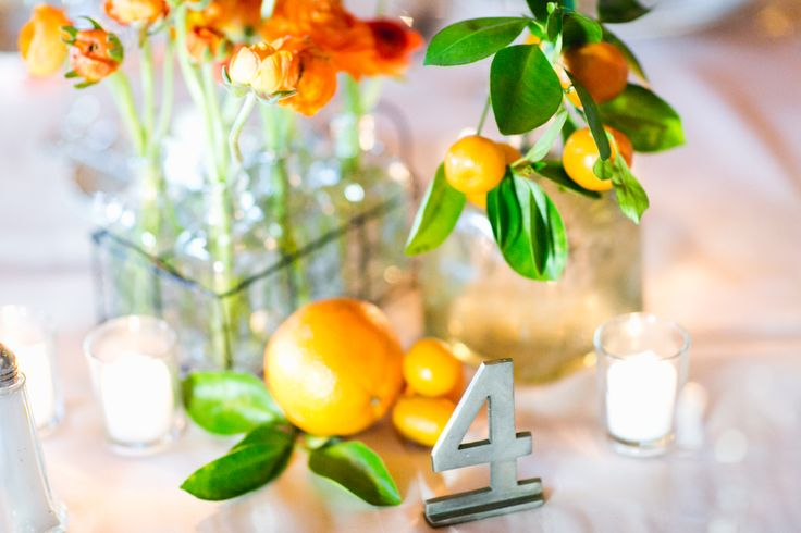 reception table arrangement at vintage citrus wedding. mini wire bottle crate holds stems of orange ranunculus. fresh oranges and kumquats, votives and a metal table number complete the charm.