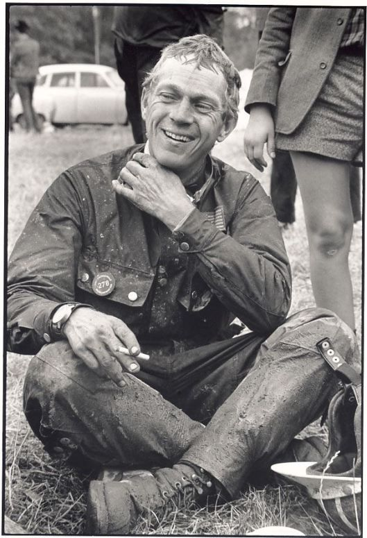 Photo – #278 Steve McQueen takes a moment on course to sit down and have a rest with his Barbour suit showing how it excels in holding back the dirt ISDT 1964 (François Gragnon)