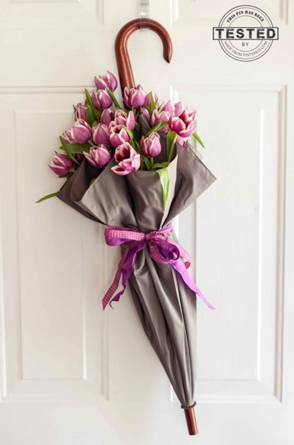 This clever display takes advantage of floral water tubes to take flowers off the tabletop and onto the door, all while wrapped in a beautiful umbrella display. It's a perfectly whimsical doorway decoration for spring!