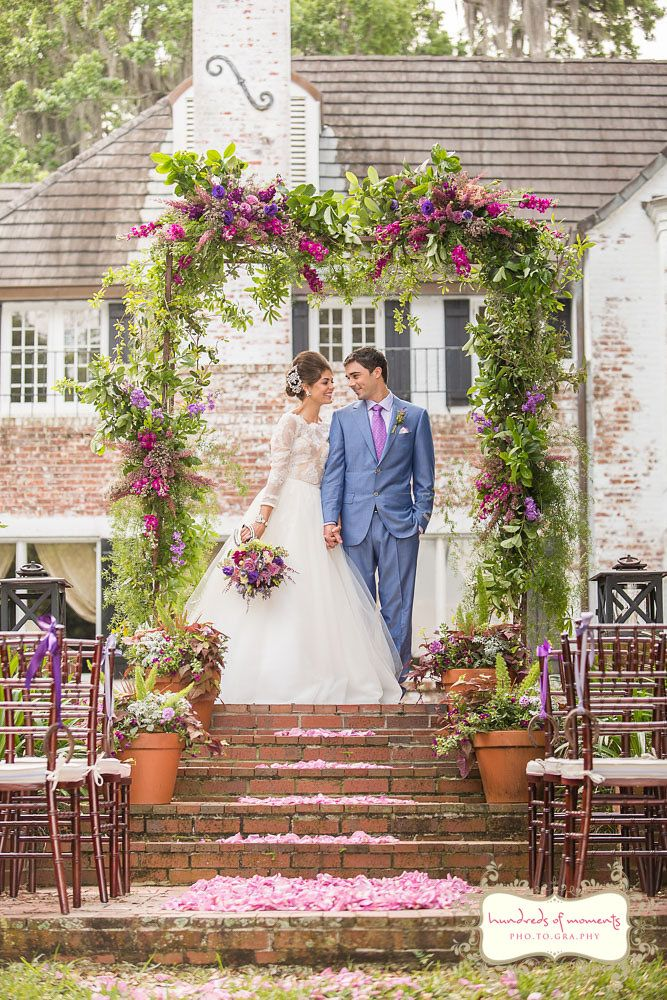 English garden inspired purple and pink floral rustic chic wedding ceremony arch at the historic Peachtree house in downtown Orlando, Florida.