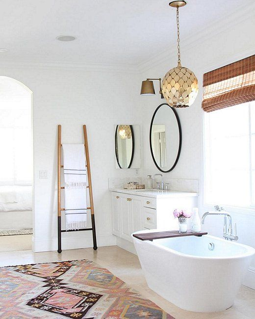 A vintage kilim area rug and glam gold pendant light completely change the vibes of this glamorous, bohemian bathroom.