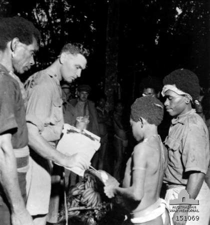 Kokoda, New Guinea. November 1942. An Australian officer in charge of the natives buys fruit from the natives at a village just recently recaptured from the Japanese. Payment is made on the barter principle including trade tobacco. Food, usually plentiful in this area, is now scarce as the retreating Japanese burned many of the native gardens.