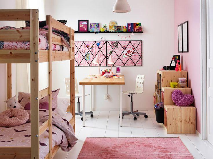 Børneværelse med en køjeseng, et skrivebord og opbevaring af massiv fyr. Kombineret med pink sengetøj, tæppe og opslagstavle.