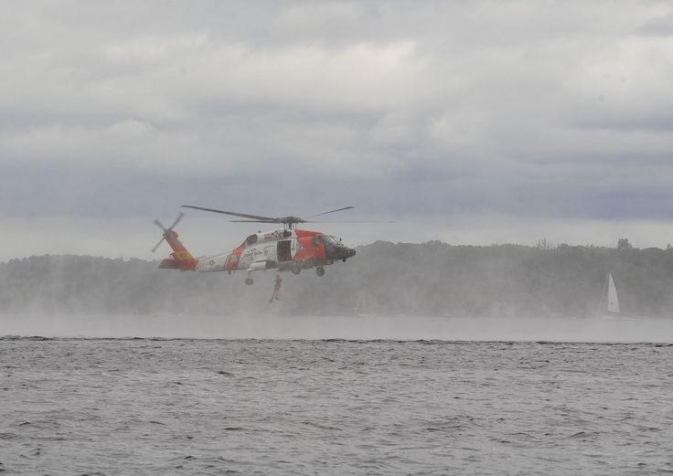 A Coast Guard rescue swimmer is dropped into Grand Traverse Bay during a rescue demonstration at the National Cherry Festival Air Show in Traverse City, Michigan, July 1, 2017. Many of the thousands of people along the waterfront saw the MH-60 helicopter, one of three that are new to Air Station Traverse City, in action for the first time. (U.S. Coast Guard photo by Master Chief Petty Officer Alan Haraf)