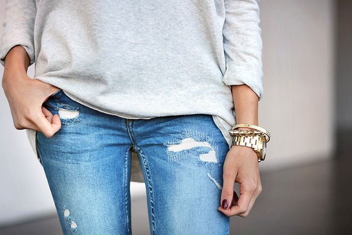 distressed denim, relaxed grey sweatshirt and gold accents