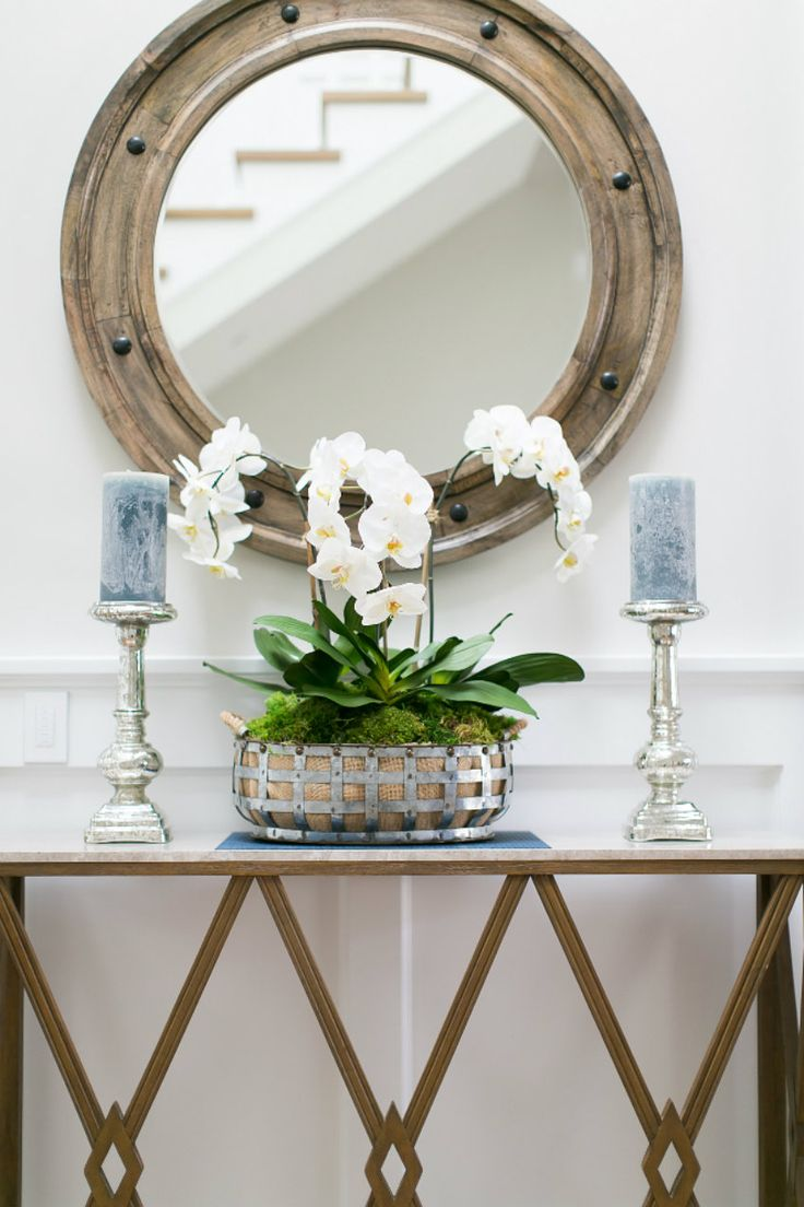 Strategically balance your Foyer decor with a classical wooden porthole mirror and a simple yet elegant console table.