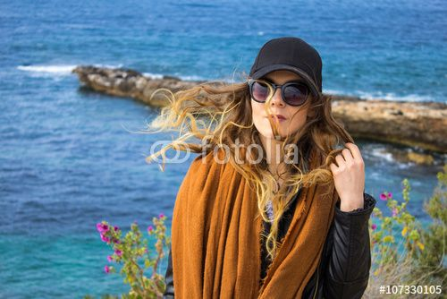 Attractive young girl with dispelled hair by the sea and rocky coast