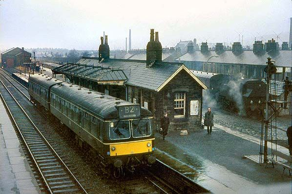 A Manchester-bound Class 113 Cravens DMU waits in the down platform at Earby station on a wet day in March 1965.