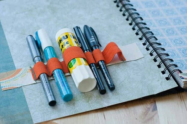 DIY school supplies holder in your notebook|                                                                 Sew an elastic band to a thick peice of paper. Be sure to create loops big enough shown in the picture to hold your suplies. After you've sewn the elastic band onto the paper, glue it to the inside of your notebook cover with a hot glue gun. Now you'll have convenient access to your pens, pencils, and other writing utensils/school supplies.