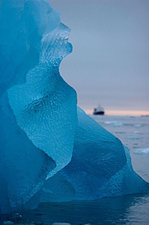Amazing image of an iceberg and cruise ship off the west coast of Svalbard.