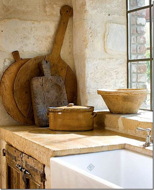Rustic antique cutting boards, farm sink, kitchen.Interior design by MILIEU editor Pamela Pierce (French, Swedish, Belgian, European, Gustavian, Scandinavian antiques, modern art, minimal, feminine, romantic, timeless, tranquil, farmhouse, elegant, traditional decor with reclaimed stone, biots, white roses, linen, slipcovers, ruffles, skirted tables, Lefroy Brooks, cremone bolts, steel windows and doors, rustic wood, white, neutrals, Chateau Domingue, oversize sconces, and chandeliers.