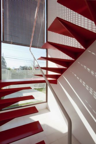 Project made in Brasil.  Detalhe da escada metálica vista por dentro. Escultórica, com acabamento em pintura epóxi vermelha, conta com um discreto corrimão branco para segurança. O sombreamento é feito pelo painel de muxarabi
