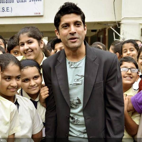 Farhan Akhtar poses with excited students during a visit to Maneckji Cooper School, in Mumbai, on July 19, 2013.