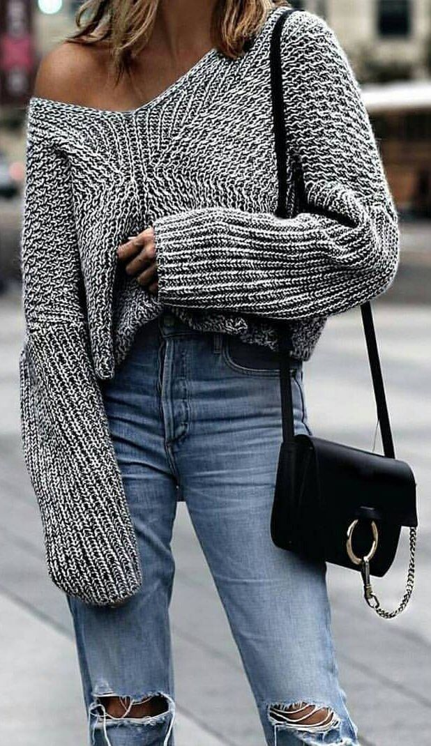 Trendy woman in a grey oversized woolen sweater and ripped boyfriend jeans