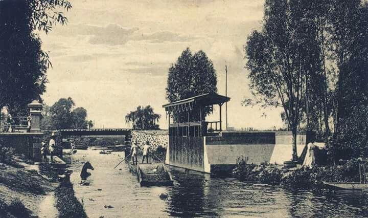 El Canal de la Viga a la altura del sifón del Río de la Piedad a principios del siglo XX.   En este sitio existió un mirador, el cual aparece a la derecha, y un embarcadero, que se aprecia del lado izquierdo. Al fondo está el puente del Ferrocarril de San Rafael-Atlixco, que corría a esa altura por un costado del Río de la Piedad.