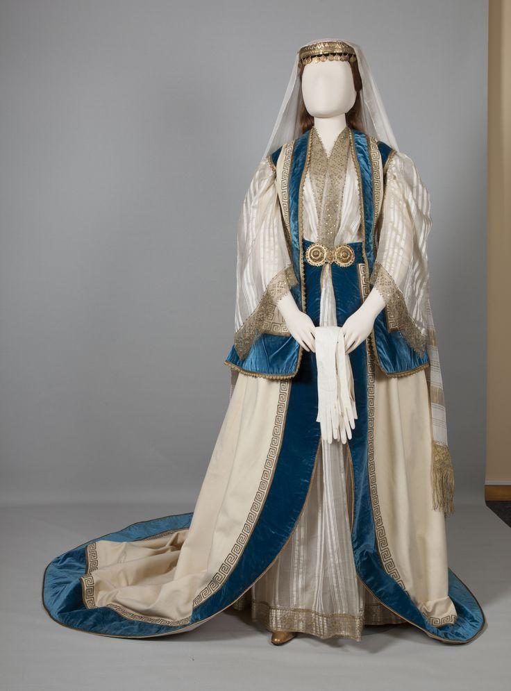 """Αύγουστος 2015: Η βασίλισσα Όλγα  δανείστηκε στοιχεία από την νυφική και γιορτινή φορεσιά της Αττικής, που ήταν εξαιρετικά διαδεδομένη στα μέλη της υψηλής κοινωνίας της Αθήνας, τα οποία προσάρμοσε στην μόδα της εποχής αλλά και στην αισθητική της επίσημης ενδυμασίας του παλατιού. Υιοθέτησε ένα υπόλευκο τσόχινο γιλέκο έχοντας ως πρότυπο τη """"γρίζα"""" της φορεσιάς των Μεσογείων καθώς και τον κεφαλόδεσμο, την ολομέταξη μπόλια και το επιμετώπιο κόσμημα εμνευσμένο από το """"ξελίτσι"""" ή """"κορωνάτσι""""."""